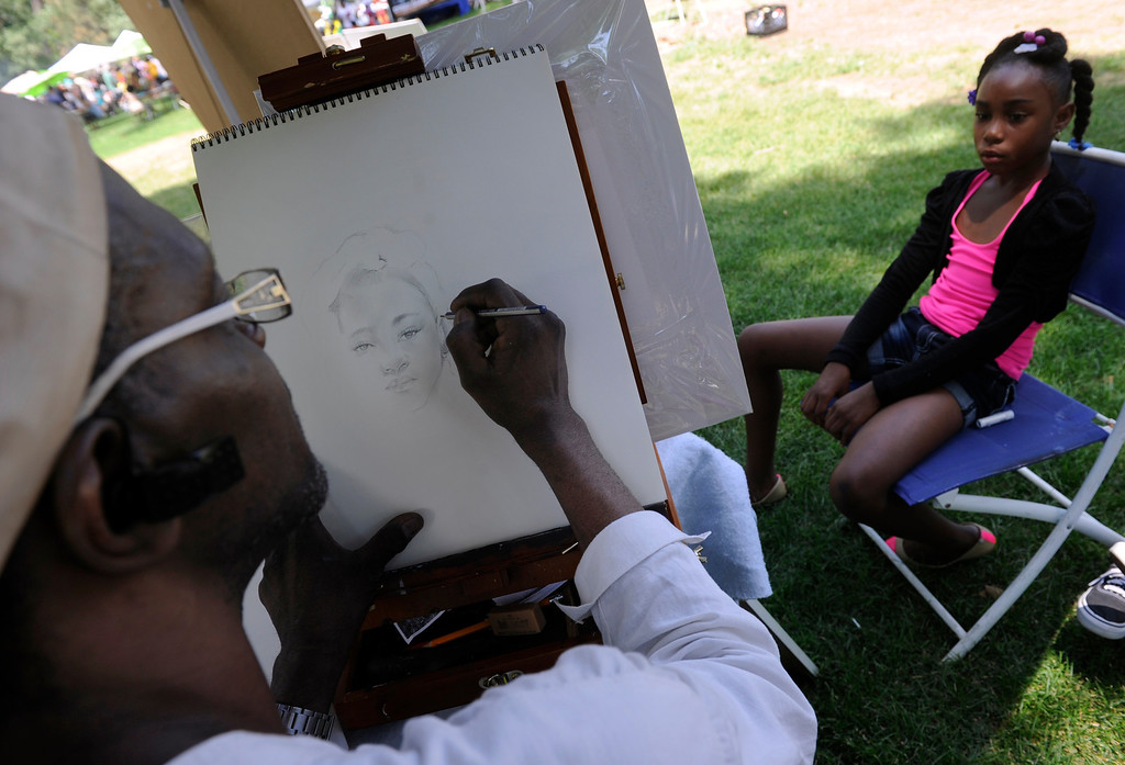 """. DENVER, CO - JULY13: Artist Robert Evans uses a pencil to make the perfect likeness of Jaelyn Odoms, 9. The 27th Annual Colorado Black Arts Festival takes place in City Park with this year\'s theme \""""African American Style: an American Legacy. The festival continues through Sunday with dozens of artists, vendors, and performances taking place. (Photo By Kathryn Scott Osler/The Denver Post)"""