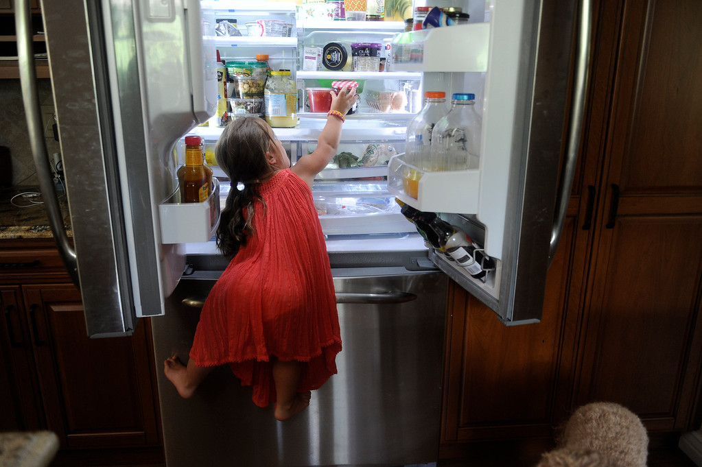 . GOLDEN, CO. - JUNE 22: Mia Towl, 9, pulls herself into the refridgerator while making lunch at her home on June 22, 2013.  (Photo By Grant Hindsley/The Denver Post)