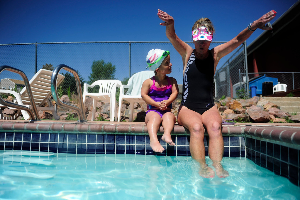 . DENVER - JUNE 19: Mia Towl, 9, looks out over the pool while her trainer, Lauria Hakala, demonstrates a stroke at Point Athletic Club on June 19, 2013. Towl begins training the summer for the 2013 Dwarf Games which take place in August.  (Photo By Grant Hindsley/The Denver Post)