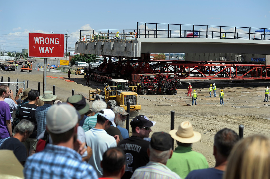 . DENVER, CO - JULY 20: Crowds of people gathered above to watch the new bridge as it begins its journey. Closing I-70 in both directions over the weekend, the Colorado Department of Transportation (CDOT) will roll the new 2,400-ton Pecos Street bridge (that will go over I-70) approximately 800 feet down I-70 using a Self Propelled Modular Transporter - the first time this method has ever been used by CDOT. The bridge will make a 180 degree turn before being set in to its final resting place. The process will take about 50 hours, with I-70 re-opening on Monday morning. (Photo By Kathryn Scott Osler/The Denver Post)