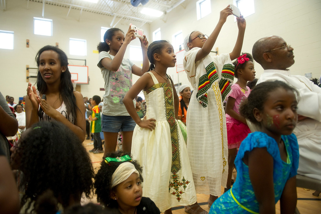 . Kids in the audience take pictures of a fashion show of traditional Ethiopian clothing at the Taste of Ethiopia Grand Festival at Laredo Elementary School in Aurora, Co, on July 28, 2013. (Photo By Grant Hindsley/The Denver Post)