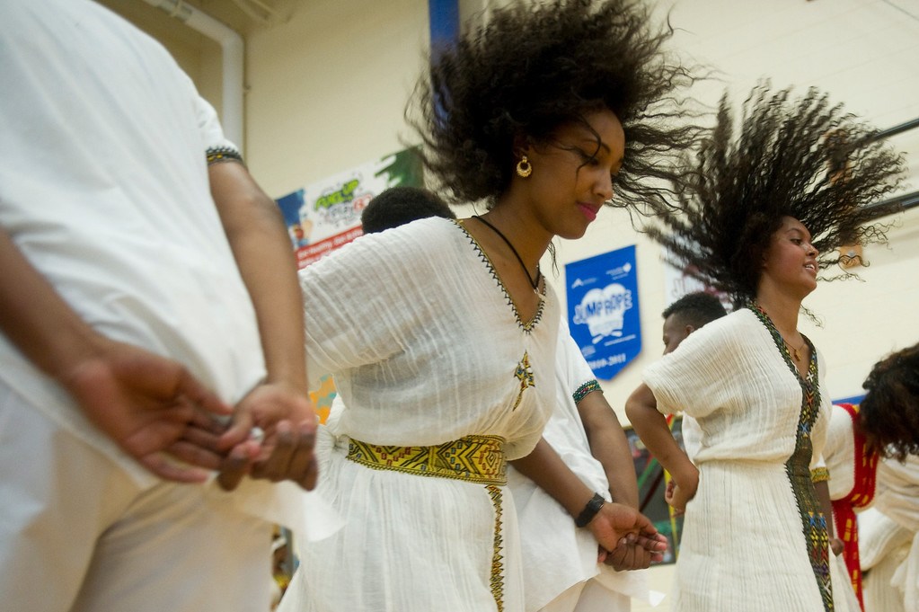 . Mahder Ferede, center, and Nardos Seyoumthe right, perform a traditional dance at the Taste of Ethiopia Grand Festival at Laredo Elementary School in Aurora, Co, on July 28, 2013. (Photo By Grant Hindsley/The Denver Post)