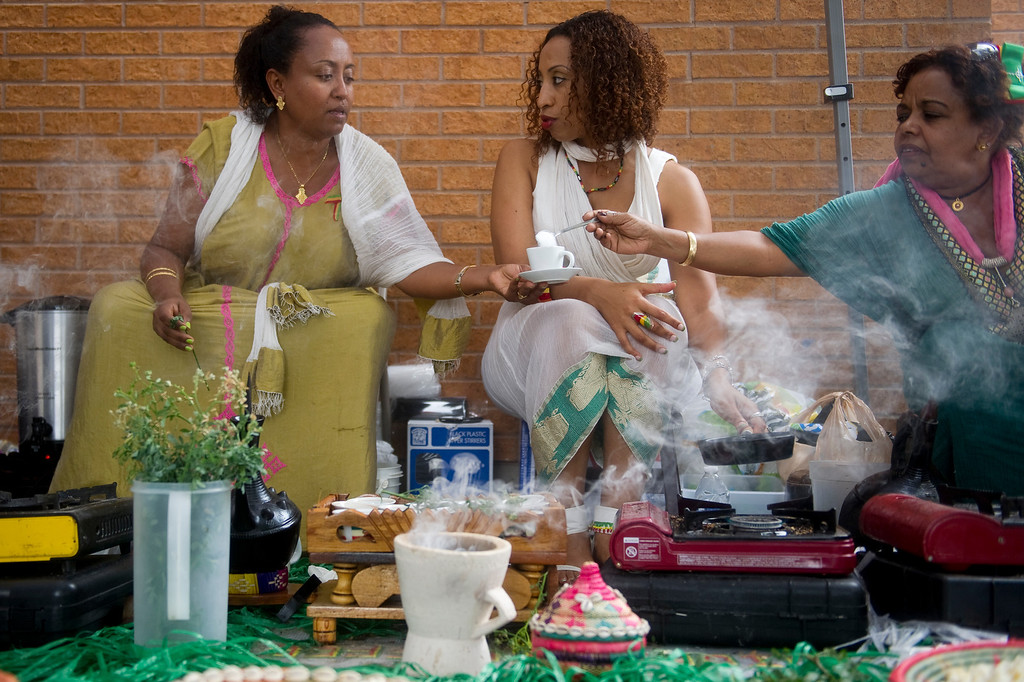 . Tegest Semegn, right, pours sugar in Hirut Yigletu\'s coffee while talking with Hiwot Lulu at the Taste of Ethiopia Grand Festival at Laredo Elementary School in Aurora, Co, on July 28, 2013. (Photo By Grant Hindsley/The Denver Post)