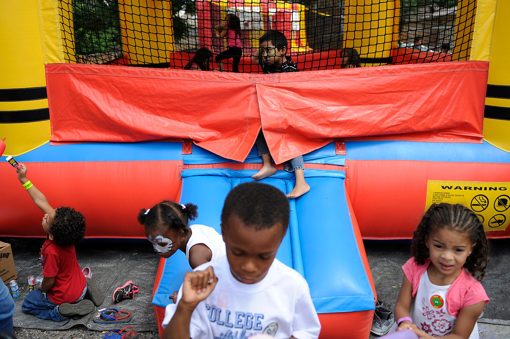 """. DENVER, CO. - AUG 3: Mayor Michael Hancock joins various events around Denver, CO on Aug. 3, 2013. The city is celebrating the first annual \""""Denver Days,\"""" a creation of Mayor Hancock.   Children climb around a bounce house at Cleave Memorial Church where a back to school extravaganza was thrown.    (Photo By Erin Hull/The Denver Post)"""