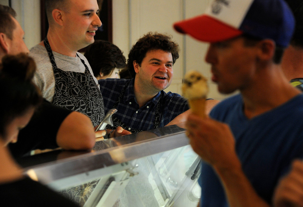 . DENVER, CO - AUGUST 03:  Comedy podcasters from Los Angeles California, Jesse Thorn, left, and Jordan Morris, center, scoop up and hand out free ice cream at the Sweet Action ice cream shop on Broadway Saturday afternoon, August 3, 2013. Morris and Thorn,  started a Kickstarter campaign to fund 1000 free ice cream cones to film a documentary.  (Photo By Andy Cross/The Denver Post)