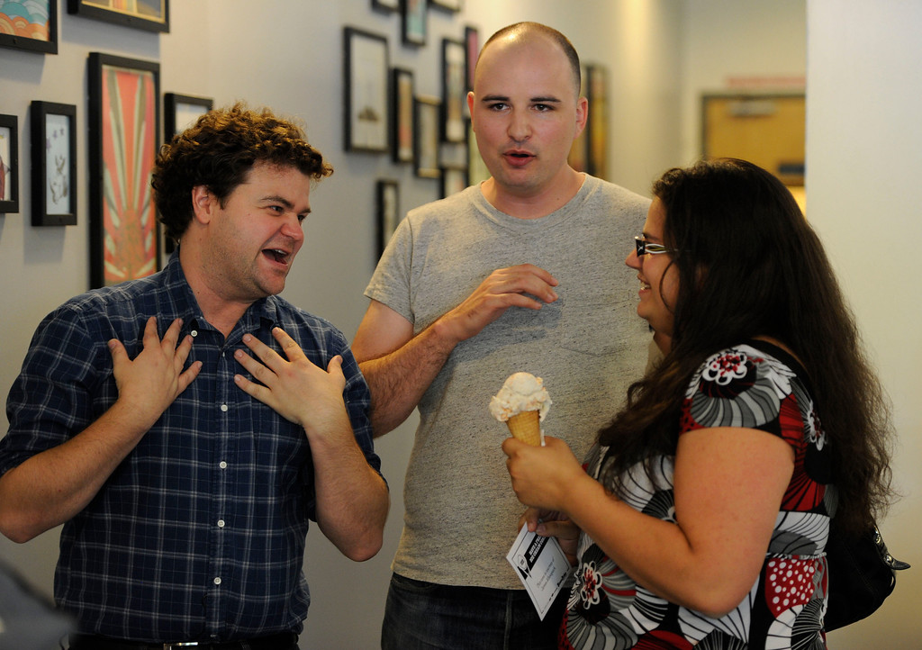 . DENVER, CO - AUGUST 03:  Jordan Morris, left, and Jesse Thorn, center, from Los Angeles California, talk with Amber Feldman, right, at the Sweet Action ice cream shop Saturday August 3, 2013. Morris and Thorn, comedy podcasters, started a Kickstarter campaign to fund 1000 free ice cream cones to film a documentary. Feldman was the first in line to get a free cone, banana with Reeces Pieces. (Photo By Andy Cross/The Denver Post)