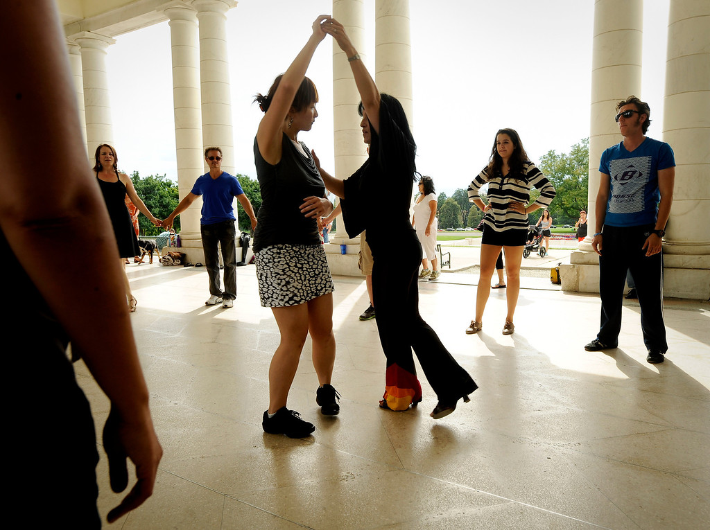 ". ""Edie, the Salsa Freak,\"" center right, teaches a group of couples to salsa dance with attitude during Salsa Central Denver\'s \""Summer Salsa and Bachata Bash\"" on August 18 where people danced zumba, salsa and bachata at Cheesman Park in the Walker Scott Cheesman Pavilion with the help of seasoned instructors. Photo by Jamie Cotten, Special to The Denver Post"