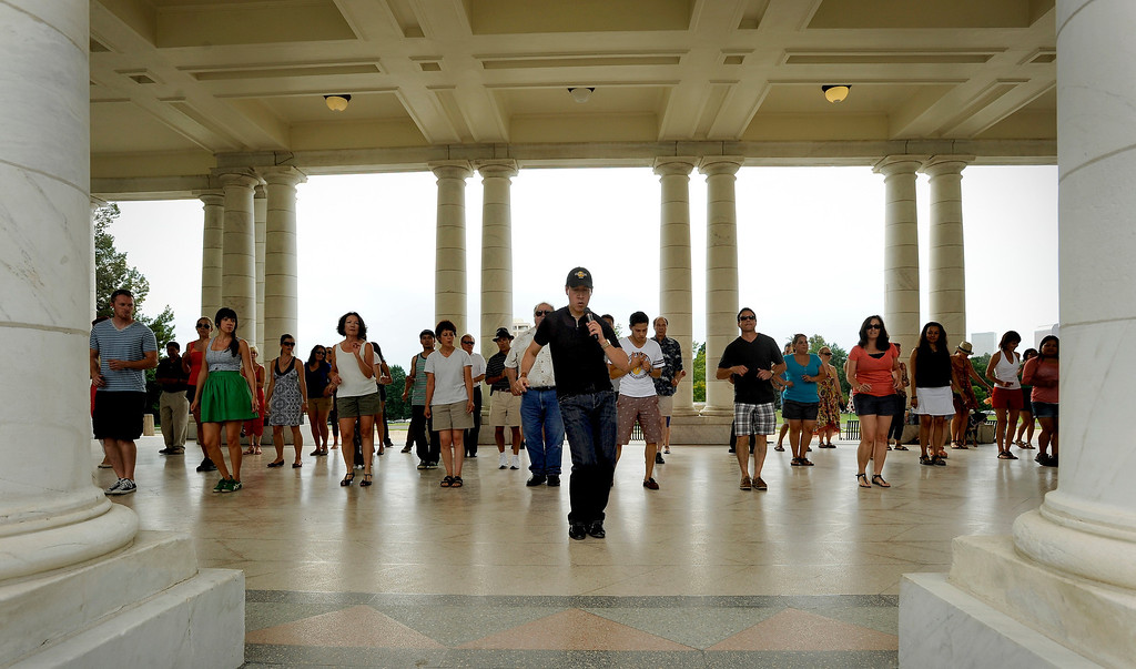 ". Rafael Ayure, center, teaches a group of people basic salsa dance steps during Salsa Central Denver\'s ""Summer Salsa and Bachata Bash\"" on August 18 where people danced zumba, salsa and bachata at Cheesman Park in the Walker Scott Cheesman Pavilion with the help of seasoned instructors. Photo by Jamie Cotten, Special to The Denver Post"