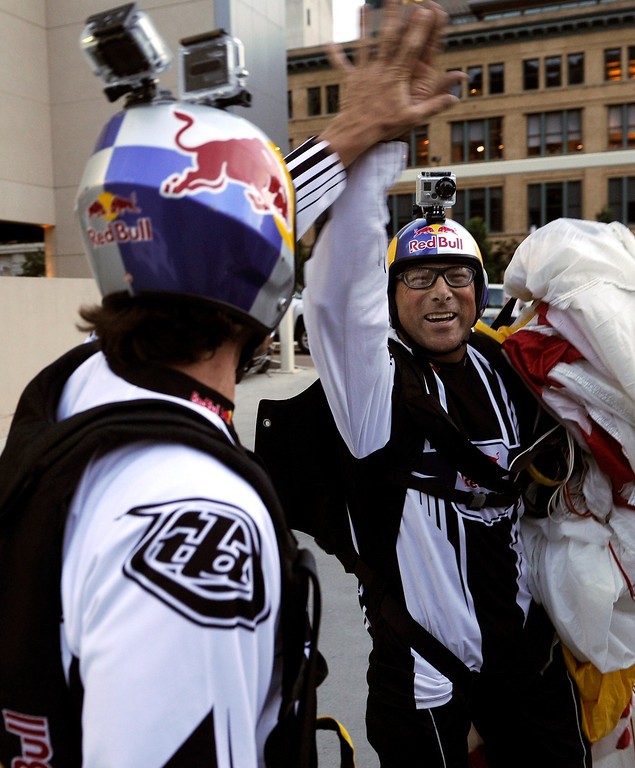 . BASE jumpers Miles Daisher, right, and Jeff Provenzano, left, exchanged a high-five after they leapt off the top of the Four Seasons Hotel in downtown Denver Tuesday night, August 27, 2013. Photo By Karl Gehring/The Denver Post