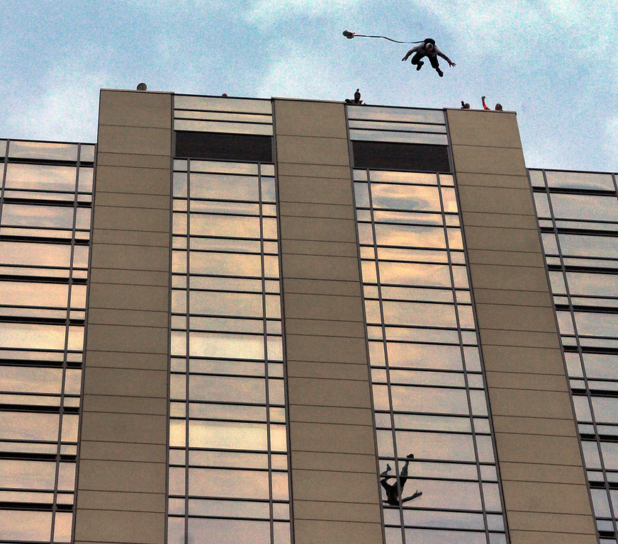 . BASE jumpers Miles Daisher and Jeff Provenzano lept off the top of the Four Seasons Hotel in downtown Denver Tuesday night, August 27, 2013 before they each deployed a canopy to make a safe landing in the parking lot. Both athletes are part of the Red Bull Air Force and jumped for a charity event at the hotel.  Photo By Karl Gehring/The Denver Post