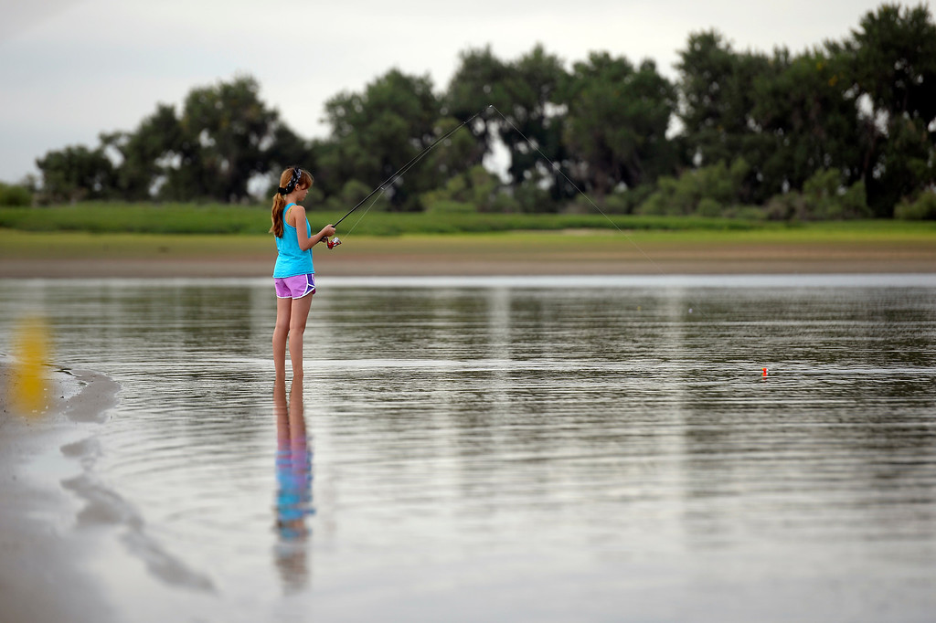 . Adriana Robinson 14, wades in the water along the shore line to get in some fishing at Barr Lake September 1, 2013. The draught conditions on the eastern plains are causing farmers to call on the water stored in Barr Lake. Good news for anglers with an appetite: As the water is drawn down to about a quarter of what\'s normally stored there, anglers can fish without limits with a license. (Photo by John Leyba/The Denver Post)