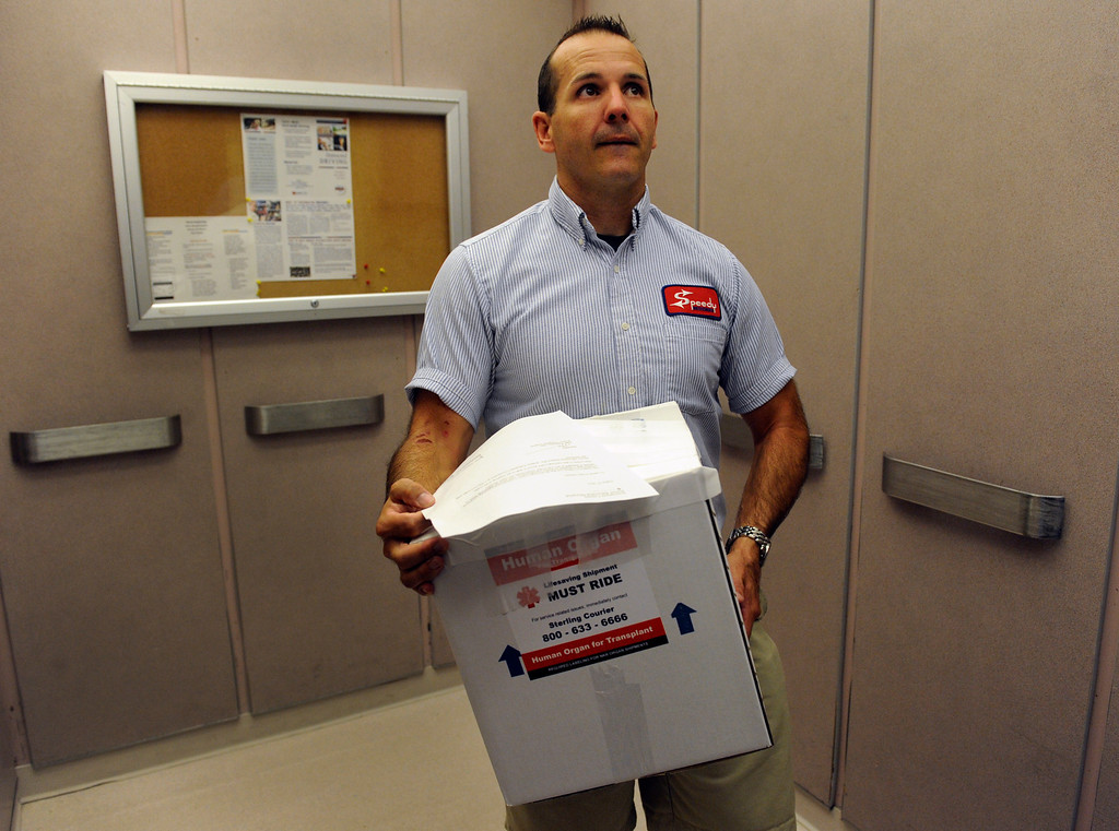 . DENVER, CO - Aug.23: After Rollman\'s specially packaged left kidney is placed in a cardboard box and has a GPS device taped to the top so that the location of the kidney can be constantly monitored,  James Thompson, a courier for Speedy Messenger, rides the hospital elevator down to the parking garage. Thompson will head to Denver International Airport in his car with the live organ and will be its escort on the commercial flight all the way to the Virginia hospital. (Photo By Kathryn Scott Osler/The Denver Post)