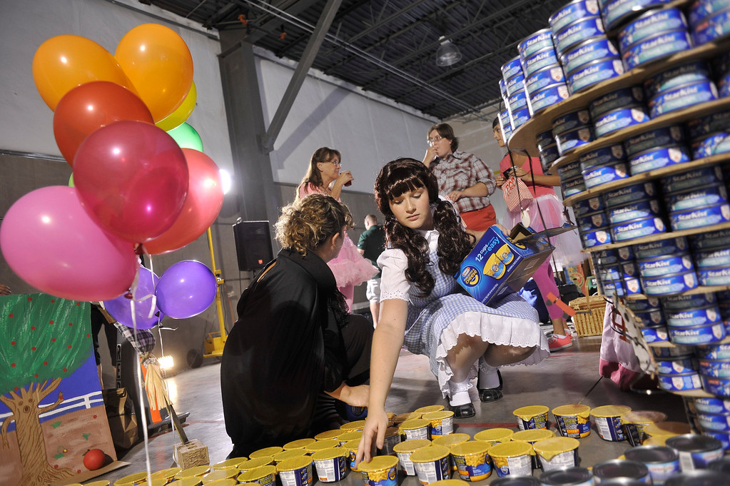 . ARVADA, CO. - SEPTEMBER 13: Lacey Rigg, dressed as Dorothy, builds a yellow-brick road from instant macaroni and cheese packages during the HindmanSanchez Law Firm\'s annual Community Can-Can food donation drive and sculpture contest in Arvada Friday afternoon, September 13, 2013. The event brought in 20,871 pounds of food and additional cash donations for Food Bank of the Rockies. (Photo by Patrick Traylor/The Denver Post)