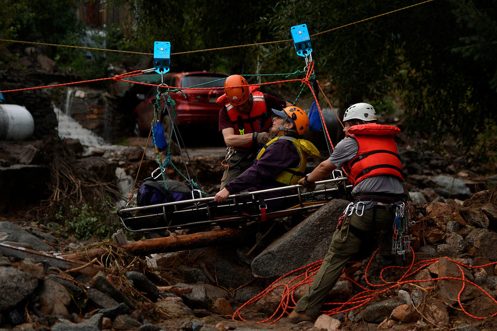 . SALINA, CO. - September 13: Darian Shaw of Salina being rescued by the Alpine Rescue Team using a high line and a sling across 4 Mile Canyon, she was brought across the rushing water with 3 other neighbors. The Alpine Rescue Team, 4 Mile Fire and the Rocky Mountain Rescue Team worked to get people out after heavy rains caused flash flooding and washed away most of Salina in 4 Mile Canyon September 13, 2013 Salina, Colorado. (Photo By Joe Amon/The Denver Post)