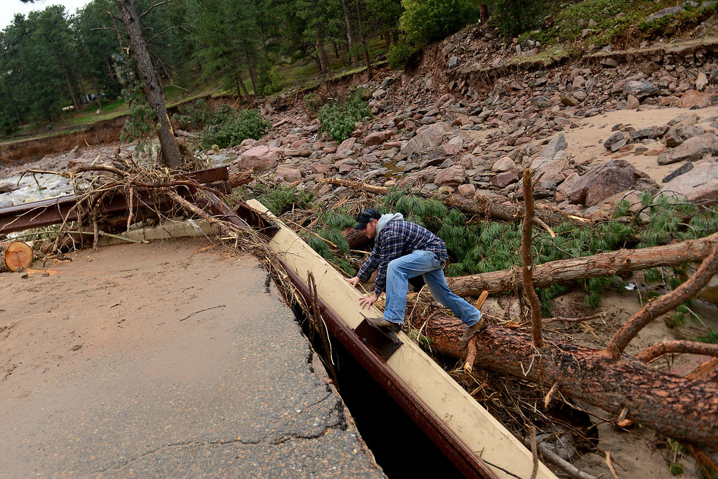. Pinewood Springs resident Judd Payne scrambles up debris on what is left of a bridge on Cree Court and Iroquois Road in his neighborhood in Pinewood Springs, Co on September 22, 2103.  Cree Court road and the bridge that went over the Little Thompson river  is completely washed out.  Prior to the flood, Payne says this area had beautiful trees and grasses and that Iroquois Road used to run next to the river.  Iroquois is completely gone. Now the area looks like a new empty river bed with large boulders and debris everywhere.   Pinewood Springs is basically an island with all main roads and bridges washed away.    (Photo By Helen H. Richardson/ The Denver Post)