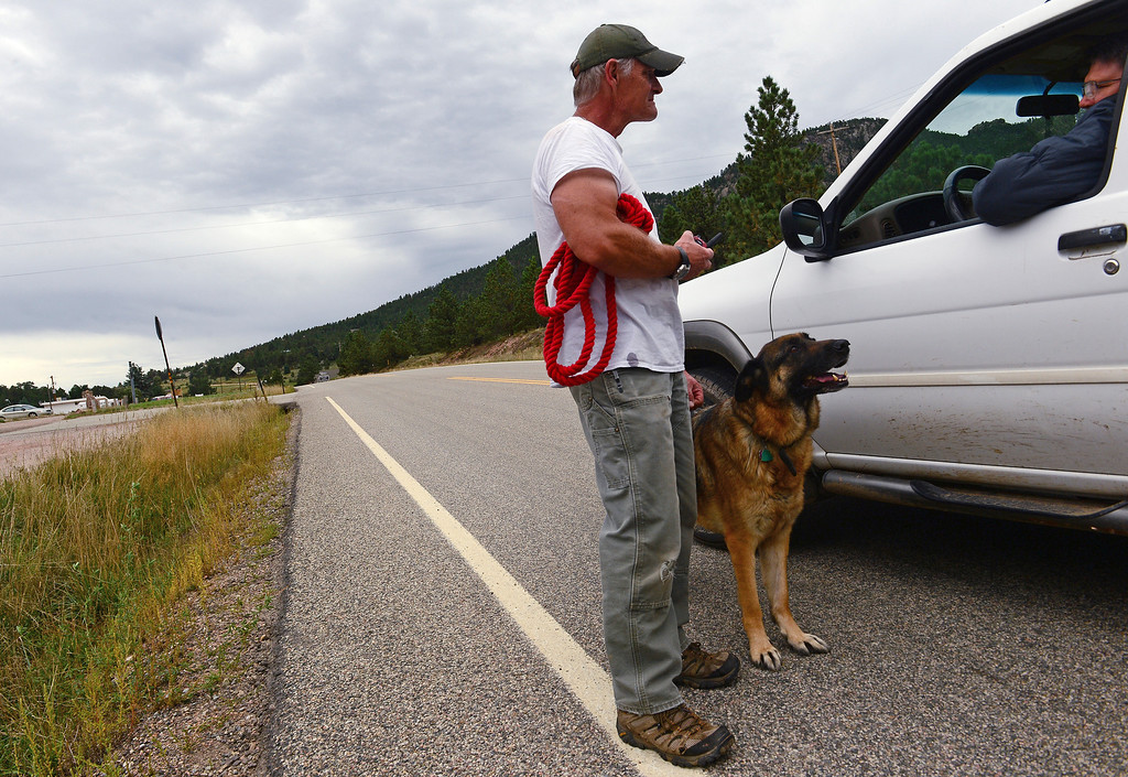 . A Pinewood Springs resident, who wanted to be known only as Brian, left, with his dog Rosie, and John Koch, in car, act as guards and neighborhood watchmen along Highway 36 as it goes through Pinewood Springs, Colo., on September 22, 2013. Because the community was evacuated during the floods, residents who stayed behind are protecting their neighborhoods. The residents have also taken things into their own hands.  They have hand built  trails so they can go west to get to Estes Park.  (Photo By Helen H. Richardson/ The Denver Post)