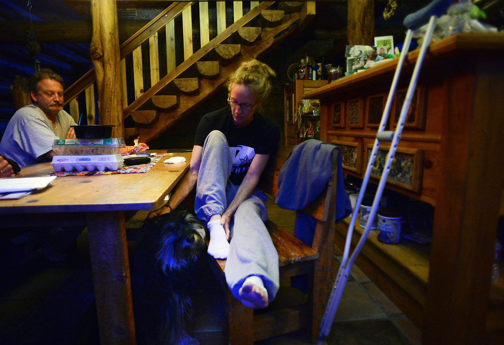 . Pinewood Springs resident Letia Grosser, pets her dog Zoe, while sitting at her kitchen table in her home in Pinewood Springs with her husband Thomas on September 22, 2013  Despite a broken knee, being on crutches, her husband, at the time, in Russia for work and multiple urgent requests to evacuate, she stood firm and stayed at home with her two dogs during the floods.   Pinewood Springs is basically an island with all main roads and bridges washed away.    (Photo By Helen H. Richardson/ The Denver Post)