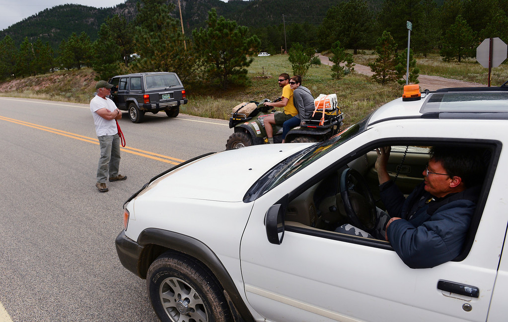 . A Pinewood Springs resident, who wanted to be known only as Brian, left, and John Koch, right in car, act as guards and neighborhood watchmen along Highway 36 as it goes through Pinewood Springs. Because the community was evacuated during the floods, residents who stayed behind are protecting their neighborhoods.  (Photo By Helen H. Richardson/ The Denver Post)