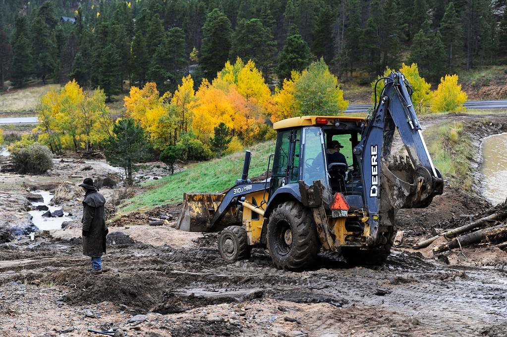 . ESTES PARK, CO - SEPTEMBER 27: Ricky Elliott, left, a wrangler at the Aspen Lodge Resort and Spa near Estes Park Colorado, works with maintenance worker, Javier Martinez, driving a backhoe, trying to repair a culvert at the lodge that was damaged by recent flooding and a landslide seen Friday afternoon, September 27, 2013. The Aspen Lodge was heavily damaged by recent flooding and the landslide that damaged power lines, pipes, the water treatment system, electric lines and washed out all fire access roads. The owner of the lodge, Yun Xiang Tseng, known as Master Chen, a Taoist Priest, is still holding seminars at the lodge, on a limited basis, but has closed the lodge to the public for at least six months to recover and rebuild. (Photo By Andy Cross/The Denver Post)