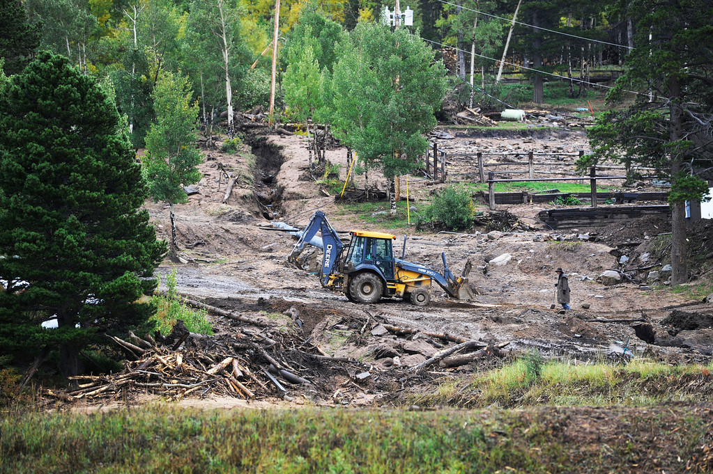 . ESTES PARK, CO - SEPTEMBER 27: Ricky Elliott, right, a wrangler at the Aspen Lodge Resort and Spa near Estes Park Colorado, works with maintenance worker, Javier Martinez, driving a backhoe, trying to repair a culvert at the lodge that was damaged by recent flooding and a landslide seen Friday afternoon, September 27, 2013. The Aspen Lodge was heavily damaged by recent flooding and the landslide that damaged power lines, pipes, the water treatment system, electric lines and washed out all fire access roads. The owner of the lodge, Yun Xiang Tseng, known as Master Chen, a Taoist Priest, is still holding seminars at the lodge, on a limited basis, but has closed the lodge to the public for at least six months to recover and rebuild. (Photo By Andy Cross/The Denver Post)