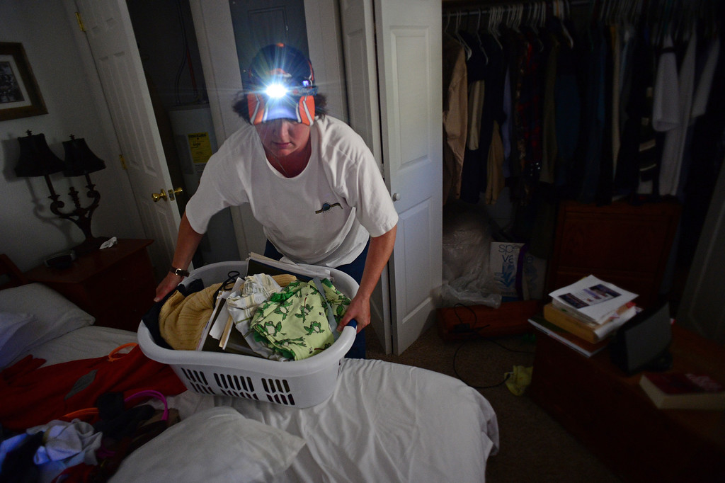 . DRAKE, CO - OCTOBER 1:  Heather McGurn uses a headlamp to get as many things out of her house in Drake, Co. October 1, 2013, before closing it for the winter.  It was the first time she and her husband Richard were allowed back into Drake to even see if their home was still standing.  The house was there but the entire property has been destroyed by the flood.  (Photo By Helen H. Richardson/ The Denver Post)