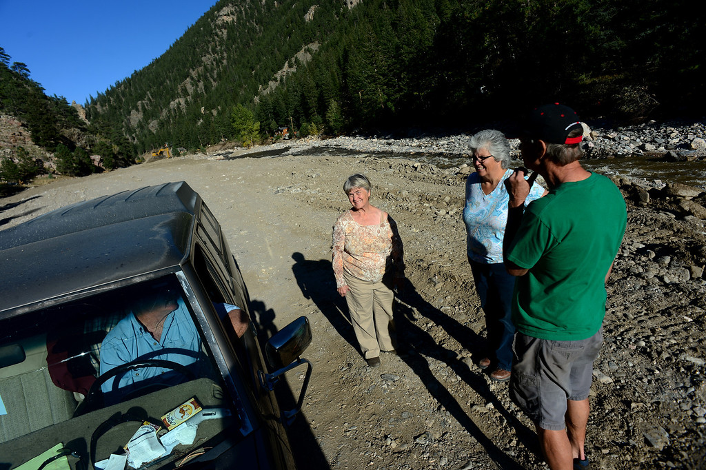. DRAKE, CO - OCTOBER 1:  Drake residents Della Darling, middle, Carin Case second from right, and her husband Leon, right, talk with Richard McGurn in the middle of  the new Highway 34 near Waltonia, Co on October 1, 2103.  The highway through Drake and east to Lyons is mostly gone in many portions.   Drake residents were allowed back into their homes for a limited amount of time to see if their homes were still there and to gather personal effects.   Many of the homes are still standing but the surrounding property, the bridges and the many portions of the highway are destroyed.  (Photo By Helen H. Richardson/ The Denver Post)
