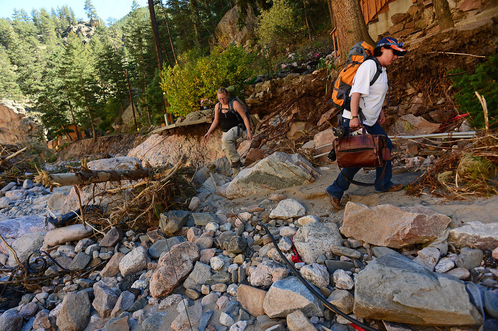 . DRAKE, CO - OCTOBER 1:  Amber Okuley, left, negotiates what used to be a road as she helps her friend Drake resident Heather McGurn, right, carry out as many personal items from McGurn\'s house in Drake, Co. October 1, 2013, before closing it for the winter.  It was the first time McGurn and her husband Richard were allowed back into Drake to even see if their home was still standing.  The house was there but the entire property has been destroyed by the flood.  (Photo By Helen H. Richardson/ The Denver Post)
