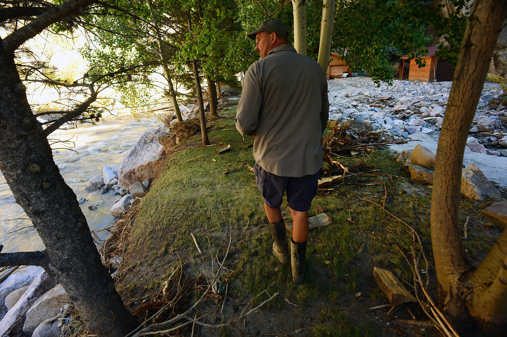 . DRAKE, CO - OCTOBER 1:  John Claus walks along his property  in Drake, Co. October 1, 2013.  The river came so high that it deposited all of the rocks at right.  Residents of the town of  Drake were allowed back into their homes for a limited amount of time to see if their homes were still there and to gather personal effects.   Many of the homes are still standing but the surrounding property, the bridges and the many portions of the highway are destroyed.  (Photo By Helen H. Richardson/ The Denver Post)