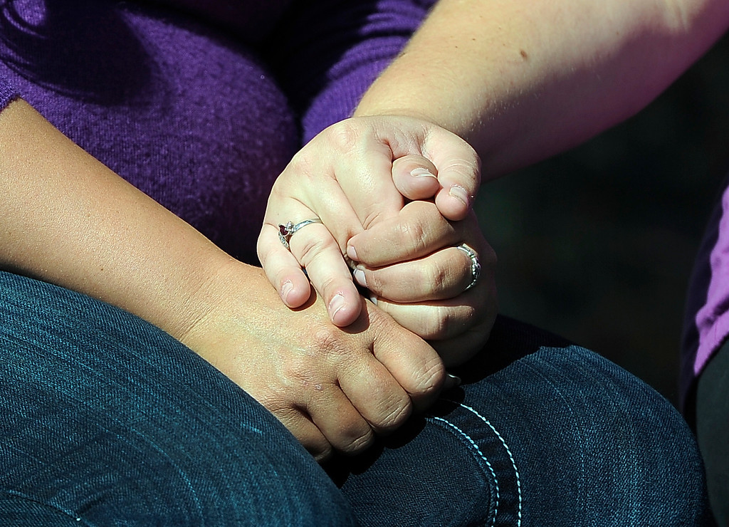 . WESTMINSTER, CO - Oct. 5: Jessica\'s mother, Sarah, right, and aunt, Rebecca, grasp their hands together as a prayer is said at the start of the dedication. A year to the day since Jessica Ridgeway went missing, a dedication ceremony takes place in her memory at the Jessica Ridgeway Memorial Park. Jessica\'s family and hundreds of others gather at the newly renovated park (much of the playground equipment made in Jessica\'s favorite color purple) that came together through the dedication of volunteers throughout the community. (Photo By Kathryn Scott Osler/The Denver Post)