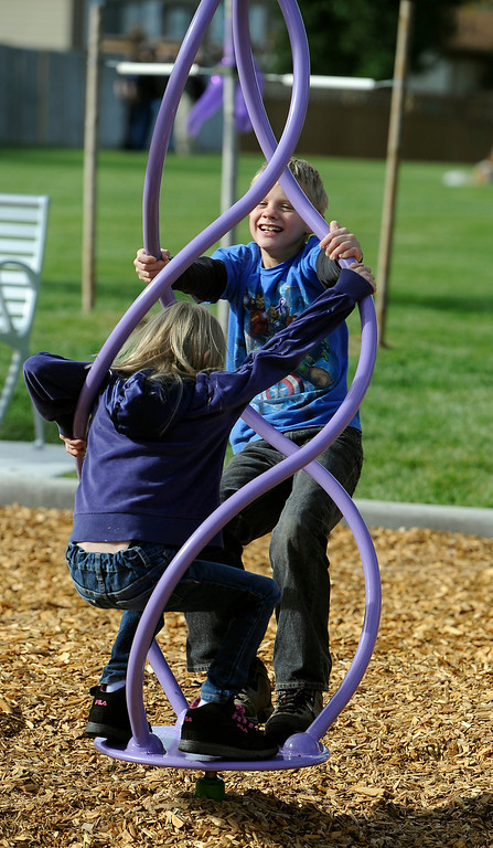 . WESTMINSTER, CO - Oct. 5: Kenneth Beach, 11, and sister Rachelle, 9, give each other a spin on the bright purple playground equipment. A year to the day since Jessica Ridgeway went missing, a dedication ceremony takes place in her memory at the Jessica Ridgeway Memorial Park. Jessica\'s family and hundreds of others gather at the newly renovated park (much of the playground equipment made in Jessica\'s favorite color purple) that came together through the dedication of volunteers throughout the community. (Photo By Kathryn Scott Osler/The Denver Post)