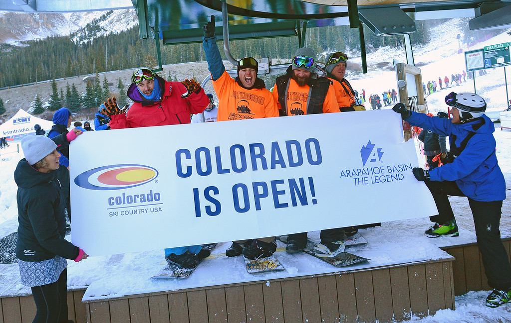 . Snowboarder Nate Dogggg, in red jacket, left, and his friends celebrate being the first ones on the lifts as Arapahoe Basin Ski area opens it\'s lifts for the first time this year on October 13, 2013.  Dogggg slept overnight to be the first one in line just as he has done for the past 18 years.  Arapahoe Basin ski area becomes the first ski area in the nation to open for the 2013-14 ski season.   The area, taking advantage of early now fall and cold conditions favorable for making snow, opened four days later than it\'s earliest opening ever on October 9th, but it is still very early. Loveland Ski Area hopes to be next in line to open for the year.  Thousands of skiers turned out for the opening of the lifts at 8:30 am.   (Photo By Helen H. Richardson/ The Denver Post)