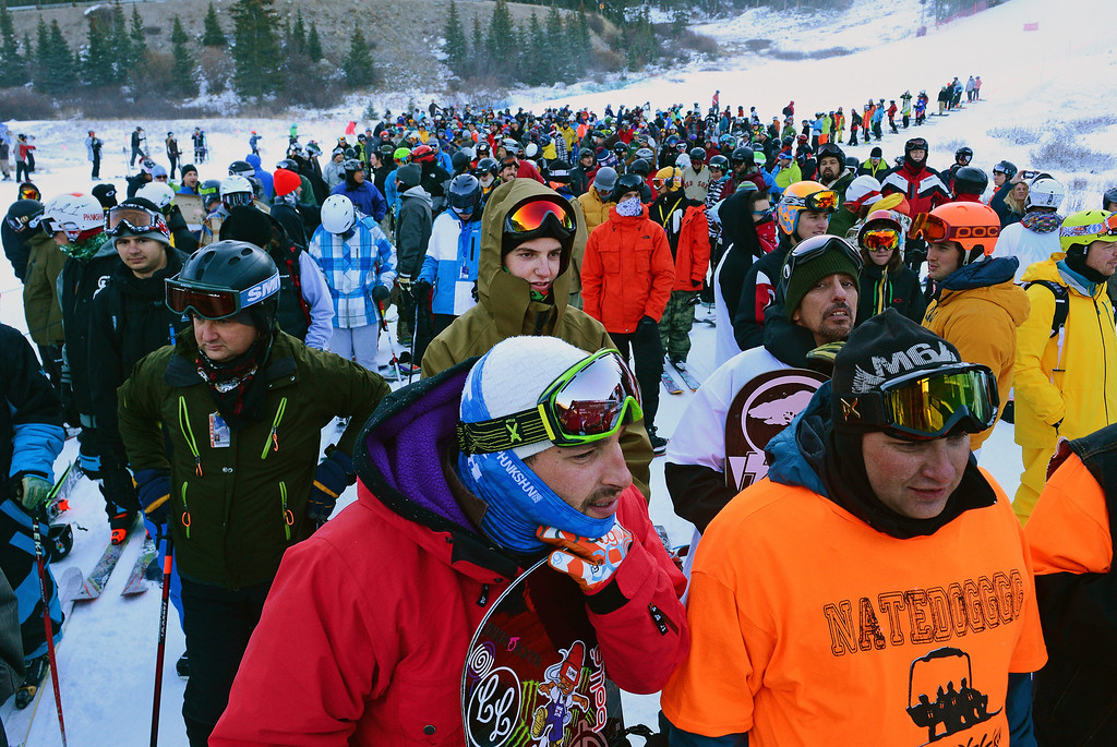 . Snowboarder Nate Dogggg, in red jacket, slept overnight to be the first one in line as he waits for the lifts to open at Arapahoe Basin Ski area in Colorado on October 13, 2013. He has been the first person on the lifts for the past 18 years.  Arapahoe Basin ski area becomes the first ski area in the nation to open for the 2013-14 ski season.   The area, taking advantage of early now fall and cold conditions favorable for making snow, opened four days later than it\'s earliest opening ever on October 9th, but it is still very early. Loveland Ski Area hopes to be next in line to open for the year.  Thousands of skiers turned out for the opening of the lifts at 8:30 am.   (Photo By Helen H. Richardson/ The Denver Post)