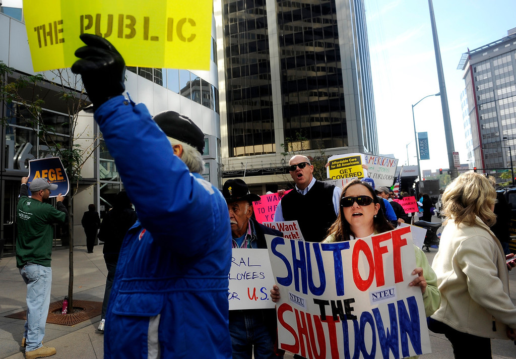 """. DENVER, CO: Oct. 16, 2013  \""""Shut Off The Shutdown\"""" reads the sign carried by Winter Torres, a worker with the National Treasury Employees Union. Torres was one of a group of demonstrators who marched in front of the shutdown Housing and Urban Development offices in downtown Denver on Oct. 16, 2013.  (Photo By Erin Hull/The Denver Post)"""