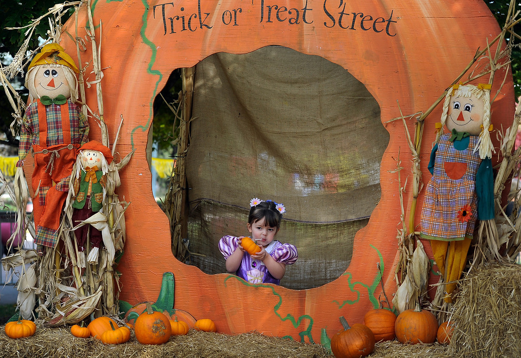 . DENVER, CO - Oct. 25: Families gather at the giant pumpkin to get photos of their trick-or-treaters. Isabella Presley, 3, dressed as Disney\'s Rapunzel, strikes a pose for mom Hollie. The Children\'s Museum of Denver hosts its annual Trick or Treat Street with trick-or-treating from the various Treat Houses, train rides on Vern\'s Mini Train, Monster Carnival, arts and crafts, and more. The event runs both Saturday and Sunday from 10 a.m to 7 p.m. (Photo By Kathryn Scott Osler/The Denver Post)