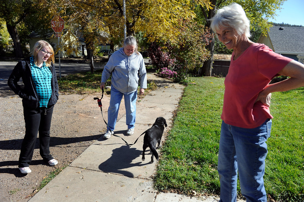 ". LYONS, CO - Oct. 26: Kathy, Byrum, center, and daughter Brittany along with ""Shadow\"" talk with neighbor Linda Johnson as the trio discusses finally have utilities restored to their homes. About 1,000 residents from the city of Lyons are expected to return home this weekend as water, sewage and gas are restored in homes. The town has been without utilities since mid-September after the St. Vrain River flooded homes and businesses and damaged the town\'s electric, water and sewer lines forcing community-wide evacuations. Crews have shattered original predicted timelines of at least three months for when utilities would be restored. (Photo By Kathryn Scott Osler/The Denver Post)"