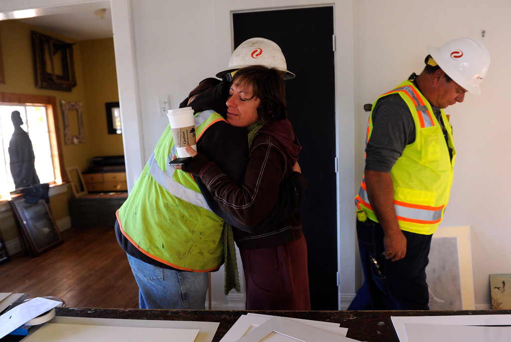 . LYONS, CO - Oct. 26: Valerie Combs, owner of The Corner Studios, is overcome with emotion as Xcel Energy journeymen from Arvada David Knoll, right, and Chris Hill (receiving a grateful hug) restore the gas to her studio and home in downtown Lyons. About 1,000 residents from the city of Lyons are expected to return home this weekend as water, sewage and gas are restored in homes. The town has been without utilities since mid-September after the St. Vrain River flooded homes and businesses and damaged the town\'s electric, water and sewer lines forcing community-wide evacuations. Crews have shattered original predicted timelines of at least three months for when utilities would be restored. (Photo By Kathryn Scott Osler/The Denver Post)