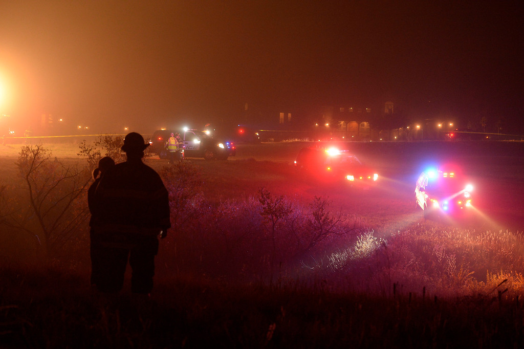 . Castle Rock firefighters look on where a small single engine plane sits on its side after crashing in a field just behind some  houses after hitting some power lines October 28, 2013 in dense fog. The pilot was taken to the hospital. (Photo by John Leyba/The Denver Post)