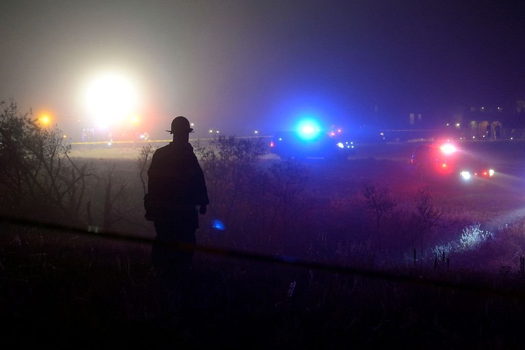 . A Castle Rock firefighter looks on where a small single engine plane sits on its side after crashing in a field just behind some  houses after hitting some power lines October 28, 2013 in dense fog. The pilot was taken to the hospital. (Photo by John Leyba/The Denver Post)