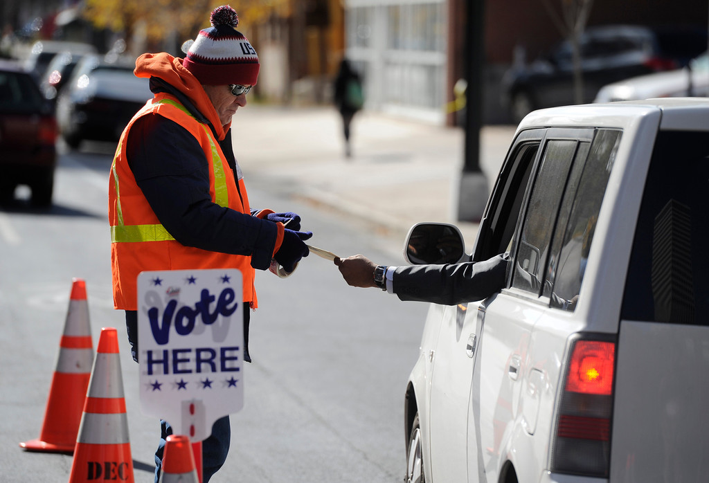 . DENVER, CO - NOVEMBER 05: Denver election judge, Tim Drago, left, takes a ballot from a voter at the drive-thru location at Denver Election headquarters Tuesday morning, November 05, 2013. (Photo By Andy Cross/The Denver Post)