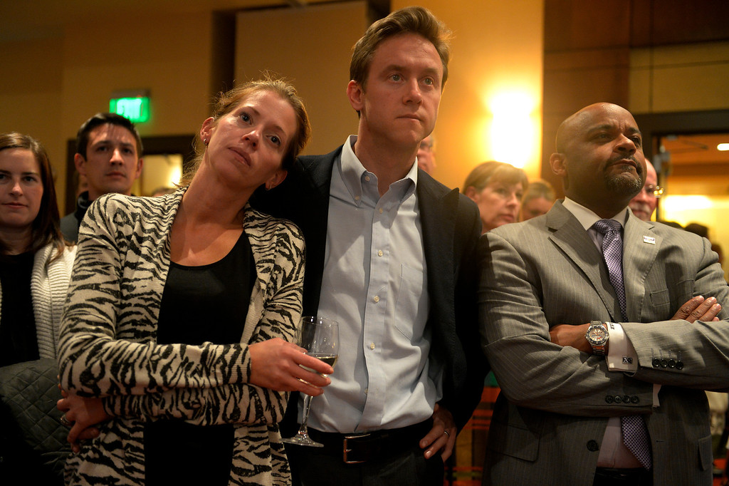 . DENVER, CO. - NOVEMBER 05: Sen. Mike Johnston and his wife Courtney are joined by Denver Mayor Michael Hancock, right, as they listen to remarks from Gov. John Hickenlooper during an Amendment 66 watch party at the Marriott City Center in Denver, CO November 05, 2013. Amendment 66 proposes a $950 million tax increase along with a restructuring of Colorado\'s K-12 school finance system. (Photo By Craig F. Walker / The Denver Post)