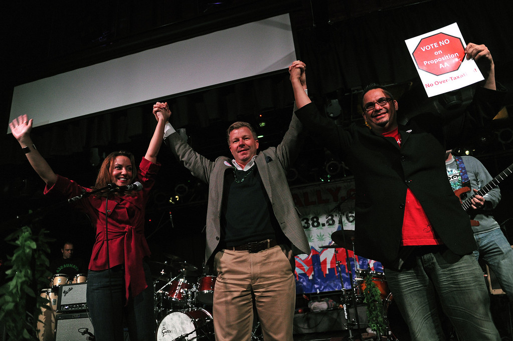 . DENVER, CO - NOVEMBER 5, 2013:  Rob Corry, middle, treasurer for the No on Proposition AA campaign, raises his hands with other members of the organization during the watch party at Casselman\'s Bar and Venue in Denver, Co on November 5, 2013.  At left is Larisa Bolivar, Executive Director of the campaign, and Miguel Lopez, volunteer coordinator, right. Proposition AA is the Colorado statewide proposition to tax marijuana. Their campaign lost but the members vow to keep up the fight.   (Photo By Helen H. Richardson/ The Denver Post)