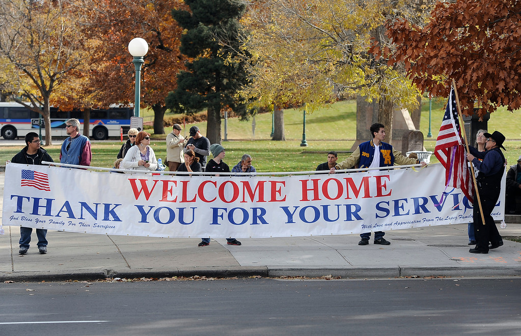 . DENVER, CO - NOV. 9: Bob Lopez, right, (holding flag) had this sign made and gets help from two grandsons and other volunteers to display it along Broadway. The largest annual Denver Veteran\'s Day Celebration takes place starting with a 5k run and continuing with a parade and remembrance ceremony downtown next to Civic Center Park, and finishing on the Auraria campus with activities and fireworks. (Photo By Kathryn Scott Osler/The Denver Post)