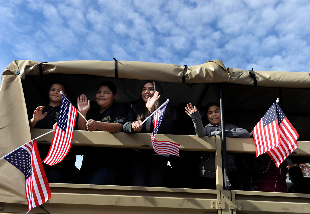. DENVER, CO - NOV. 9: A group of young women wave from a military truck honoring the U.S. Marines Corps as the parade moves along Broadway. The largest annual Denver Veteran\'s Day Celebration takes place starting with a 5k run and continuing with a parade and remembrance ceremony downtown next to Civic Center Park, and finishing on the Auraria campus with activities and fireworks. (Photo By Kathryn Scott Osler/The Denver Post)