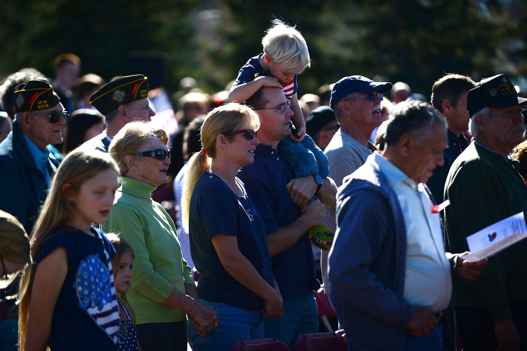 ". Paul Carr holds his son Andrew, 4 on his shoulders while he and his wife Paig sing God Bless America during the 36th annual Remembrance ceremony of Veteran\'s Day at Fort Logan Cemetery in Lakewood, CO  on November 11, 2013. The day was marked with a 21 gun rifle salute, ""Echo taps\"" played by buglers and the release of white birds of freedom.  The benediction was given by Jackie Newlander.  (Photo By Helen H. Richardson/ The Denver Post)"