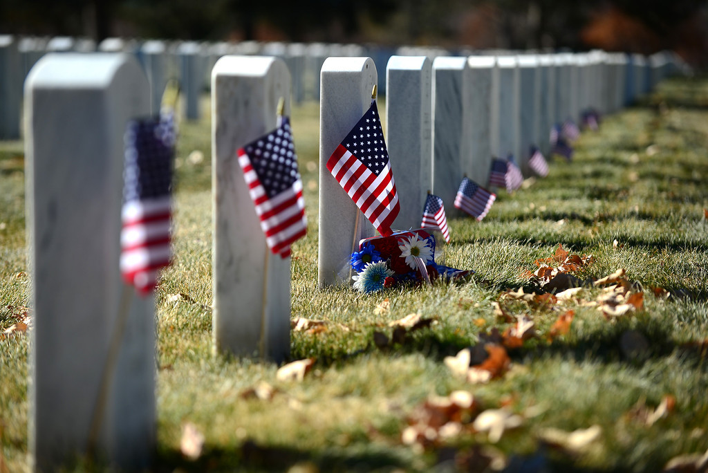 ". LAKEWOOD, CO - NOVEMBER 11, 2013: Small American flags mark the white tombstones of the graves of soldiers after the 36th annual Remembrance ceremony of Veteran\'s Day at Fort Logan Cemetery in Lakewood, CO  on November 11, 2013. The day was marked with a 21 gun rifle salute, ""Echo taps\"" played by buglers and the release of white birds of freedom.  The benediction was given by Jackie Newlander.  (Photo By Helen H. Richardson/ The Denver Post)"