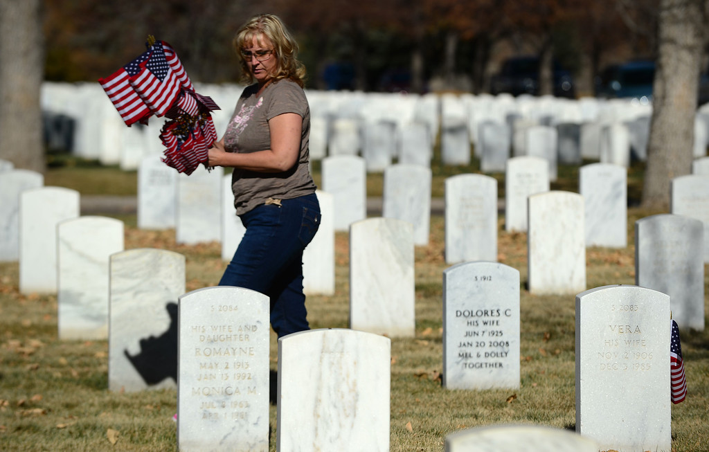 ". LAKEWOOD, CO - NOVEMBER 11, 2013: Leann Armijo, of Kiowa, puts flags on the graves of soldiers after the 36th annual Remembrance ceremony of Veteran\'s Day at Fort Logan Cemetery in Lakewood, CO  on November 11, 2013. The day was marked with a 21 gun rifle salute, ""Echo taps\"" played by buglers and the release of white birds of freedom.  The benediction was given by Jackie Newlander.  (Photo By Helen H. Richardson/ The Denver Post)"