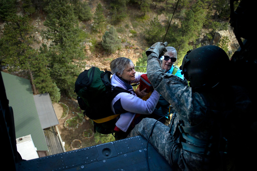 . BOULDER, CO. - September 17: Two ladies have a first look at Sgt 1st class Keith Bart as they are hoisted into a UH-60 Black Hawk near Jamestown during search and rescue flight with members of the 2-4 GSAB with the 4th ID of Fort Carson September 17, 2013 Boulder, CO. (Photo By Joe Amon/The Denver Post)