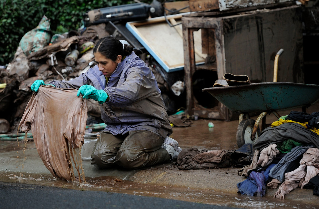 . BOULDER, CO - SEPTEMBER 14: ColleenKeane, right, tries to salvage clothing by washing it out in the gutter in front of her home near Iris Ave and 9th St. in Boulder, Colorado Monday morning, September 16, 2103. Keane rents the basement of this house which was completely flooded out from the overflowing Two-Mile Creek. Crews are working to clean up the mess, clearing all of Keane\'s and her roommate\'s belongings from the water and mud. Water reached the ceiling of the basement of the house owned by Anne Skok, left. (Photo By Andy Cross/The Denver Post)