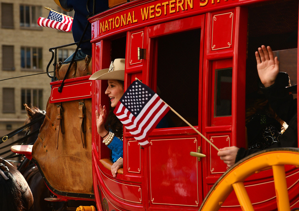 . DENVER, CO - JANUARY 9, 2014:  Malinda DeBell, Boulder County queen rides in the national western stage coach during the National Western Stock Show Parade along 17th street  in Denver, Co on January 9, 2014.  The National Western Stock Show Kick-Off Parade featured Longhorn cattle herded through the streets of downtown Denver, along with bands, horses, floats, cowboys and rodeo queens. The parade started at noon at Union Station in Lower downtown Denver and headed up 17th street.   The annual National Western Stock Show runs Jan. 11-26. Schedules and ticket information is available at NationalWestern.com.  (Photo By Helen H. Richardson/ The Denver Post)