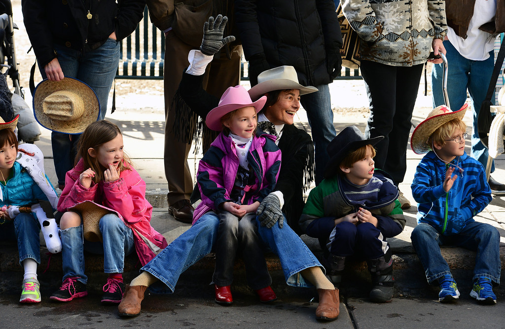 . DENVER, CO - JANUARY 9, 2014:  Edna Faris Dust sits with her grand niece Grace Faris, 5, in her lap as the two watch the National Western Stock Show Parade as it makes it\'s way up 17th street  in Denver, Co on January 9, 2014.  The National Western Stock Show Kick-Off Parade featured Longhorn cattle herded through the streets of downtown Denver, along with bands, horses, floats, cowboys and rodeo queens. The parade started at noon at Union Station in Lower downtown Denver and headed up 17th street.   The annual National Western Stock Show runs Jan. 11-26. Schedules and ticket information is available at NationalWestern.com.  (Photo By Helen H. Richardson/ The Denver Post)